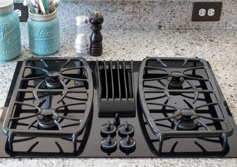 Top of detailed black gas stove on marble countertop in kitchen