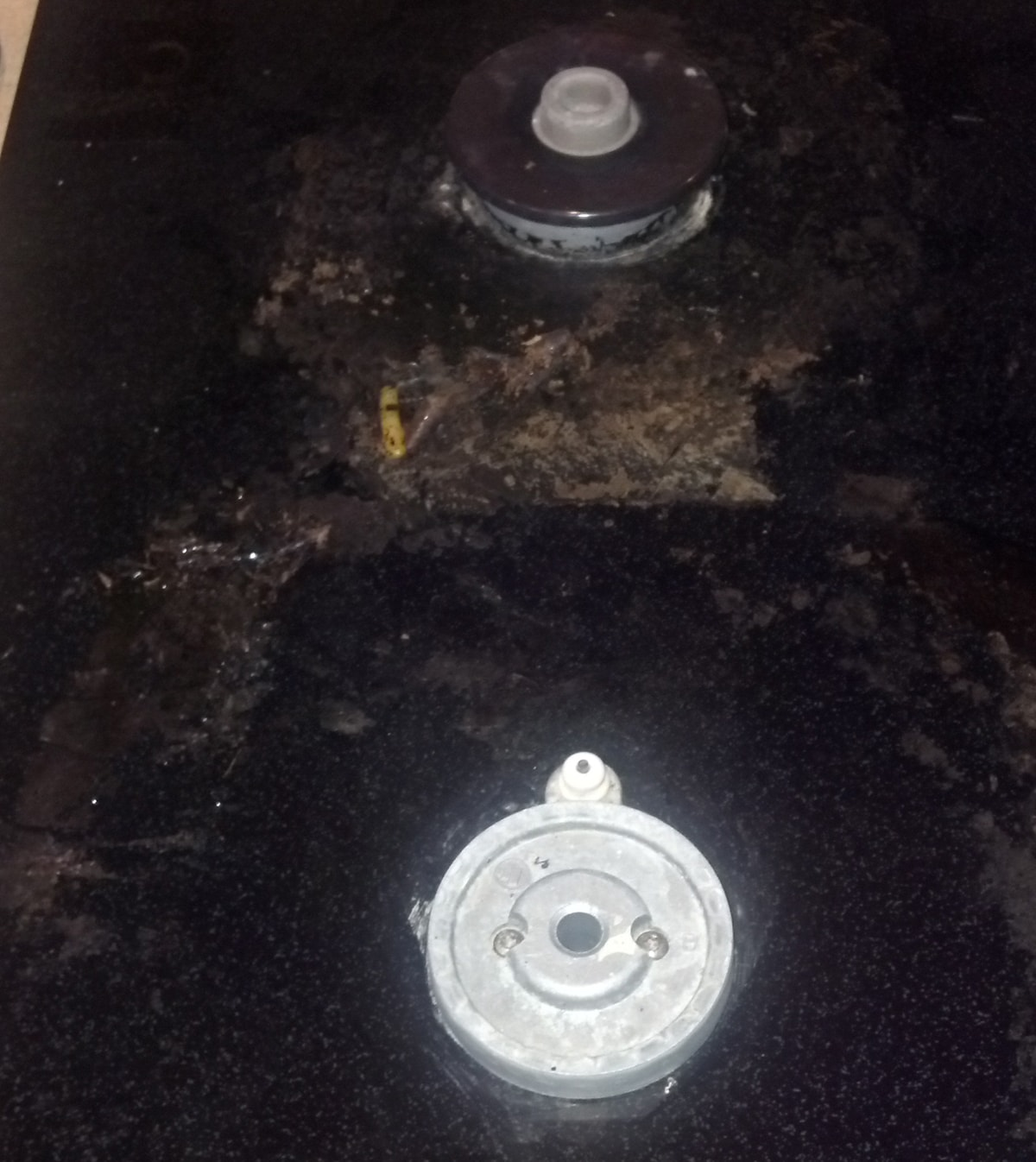 Dirty and damaged surface of a black glass stove and burner.