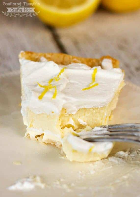 Lemon cheesecake slice with creamy whopped topping and fresh lemon zest