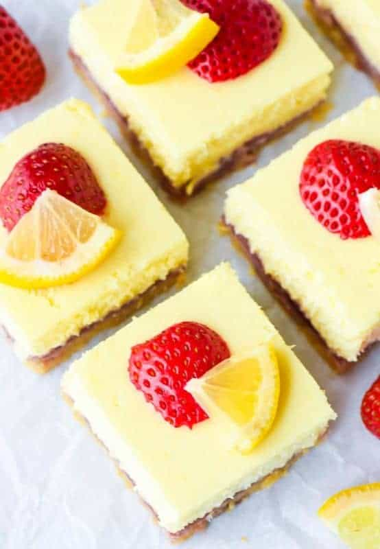 Strawberry lemon cream cheese bar squares topped with freshly slices strawberries and lemon on parchment