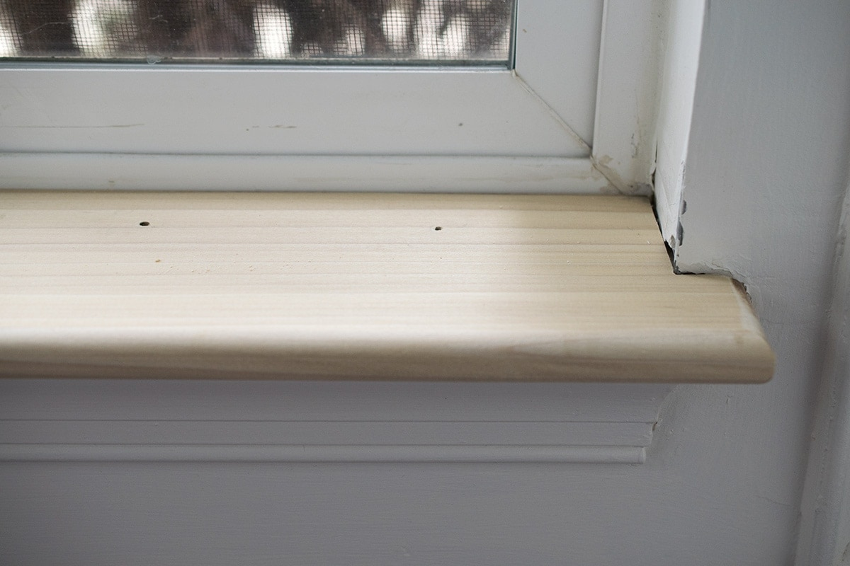 New window sill with nail holes around the edges.