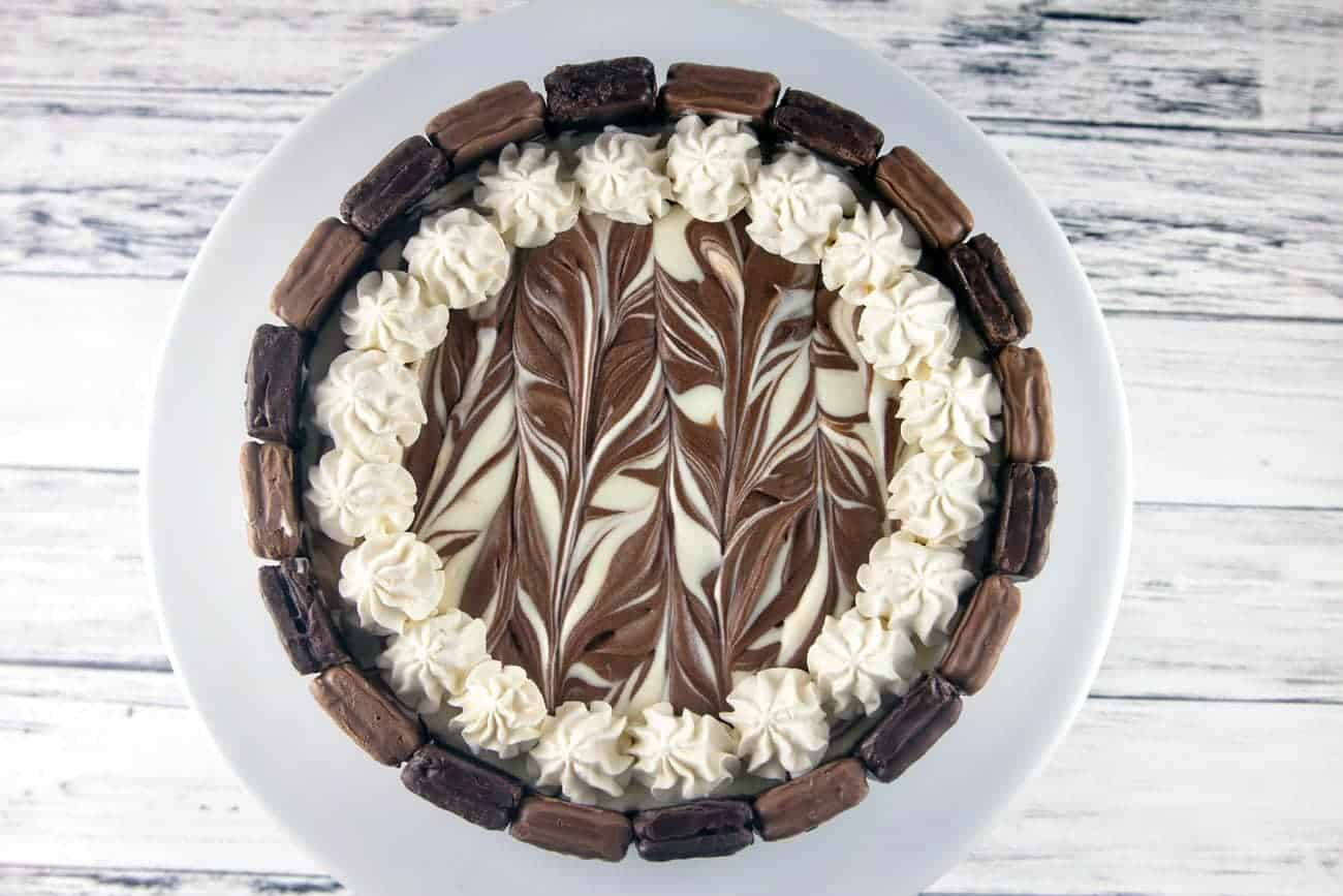 Decadent Tim Tam cheesecake with delicate chocolate swirls, whipped cream, and Tim Tam chocolate wafer cookies.