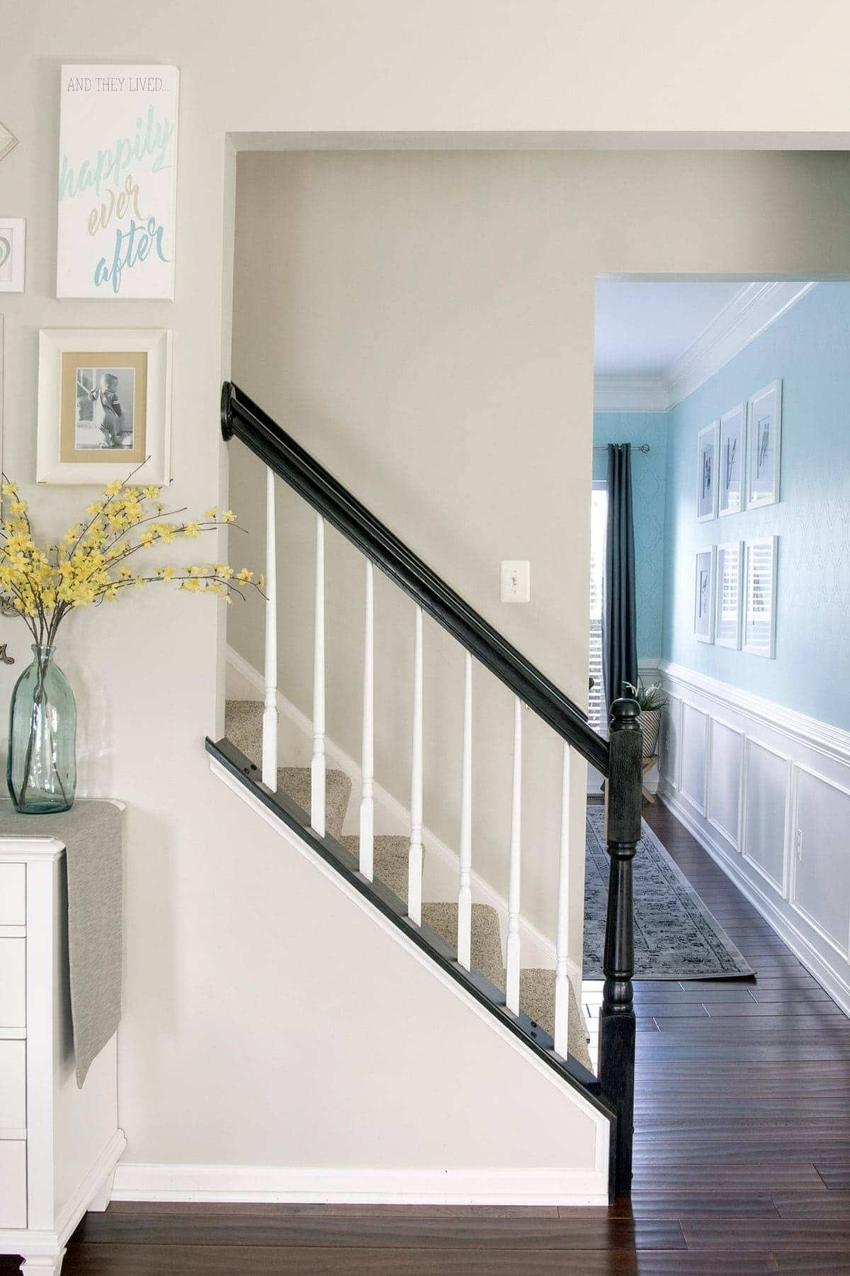 Completed oak painted stair railing with black handrail and white balusters.