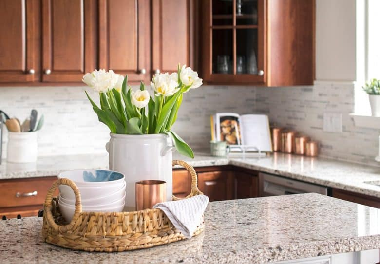 Marble breakfast bar with woven basket tray centerpiece filled with white peonies, bowls, and copper mug