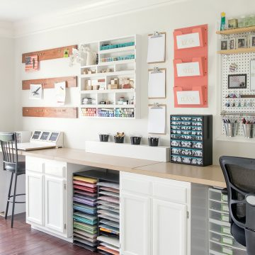 Colorful craft room with white walls and white cabinets with craft supplies on the wall and a pegboard.
