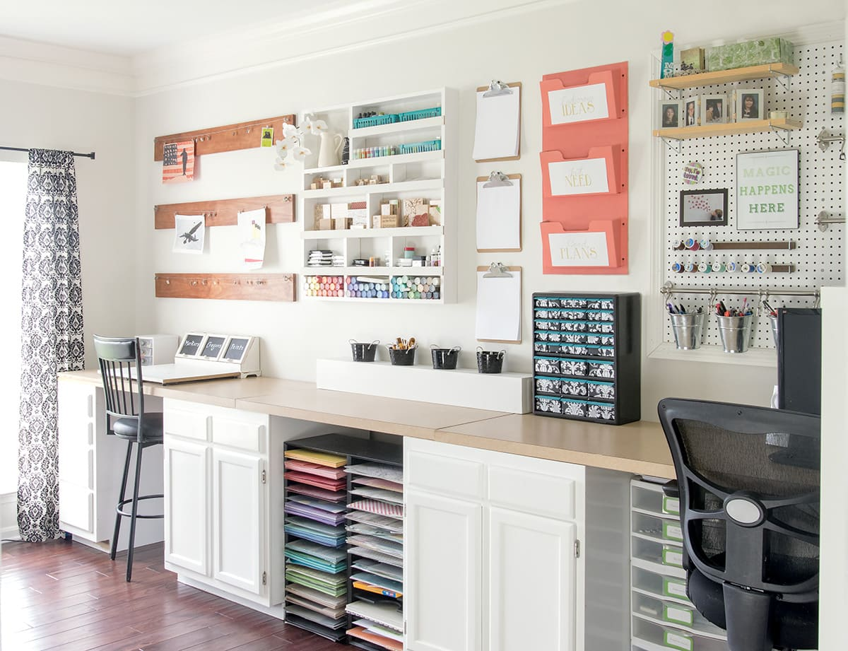 Organized craft room and office area. Space includes children's artwork display, pegboard wall hanging and custom desk with built in cabinets.