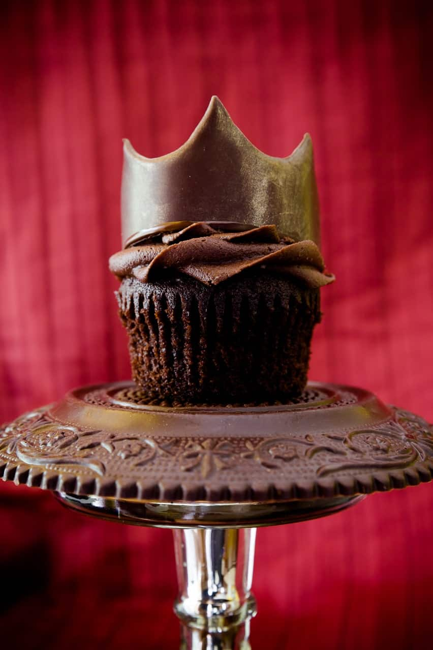 Ultimate chocolate cupcake with rich chocolate frosting with chocolate molded crown on chocolate pedestal