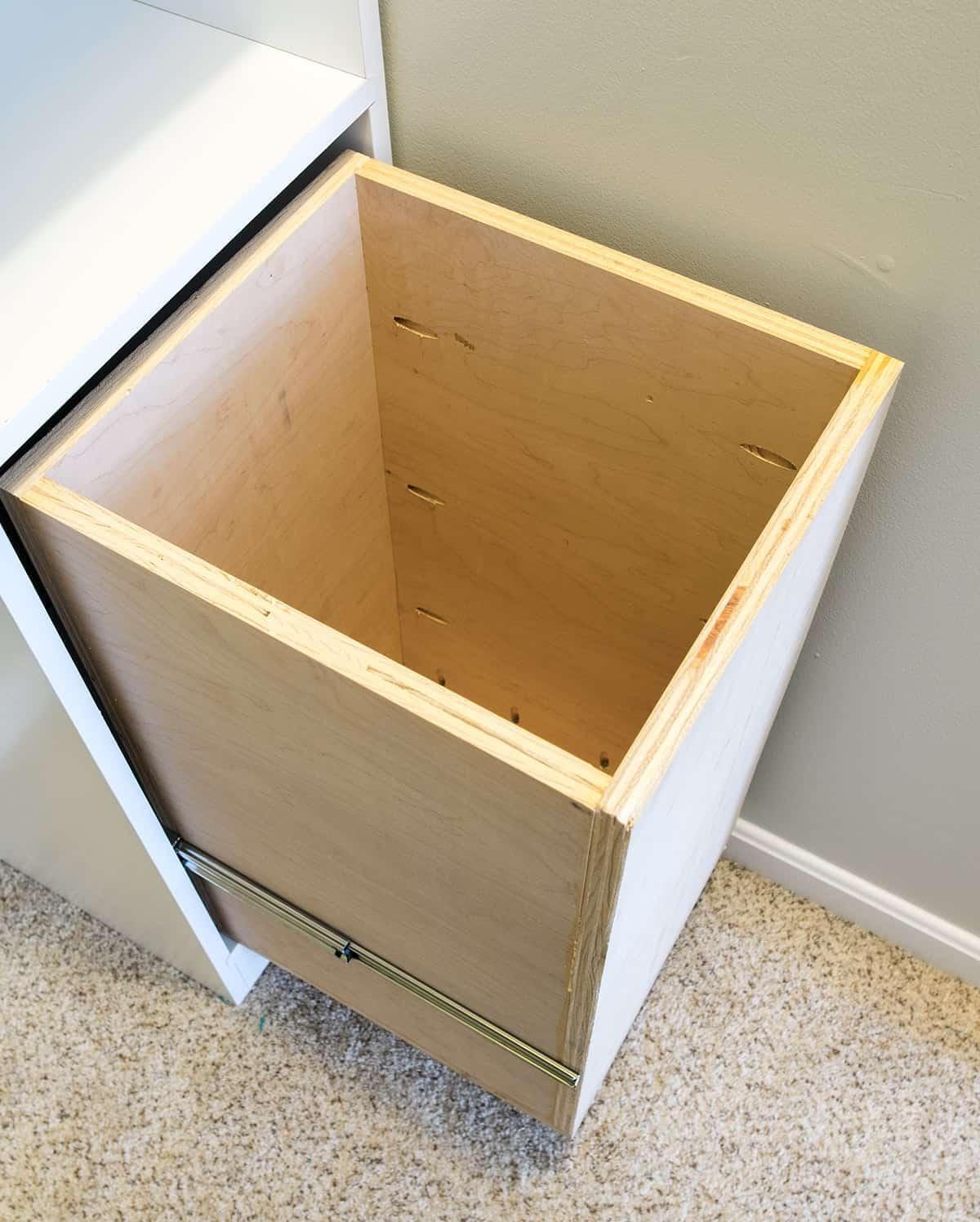 Built-in laundry basket in white custom built bedroom closet