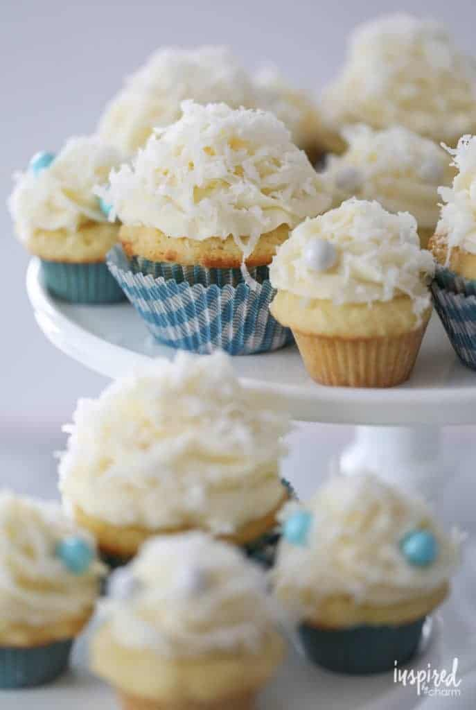 Ultimate coconut cupcakes topped with fluffy frosting and rolled in delicious coconut, garnished with delicate edible pearls