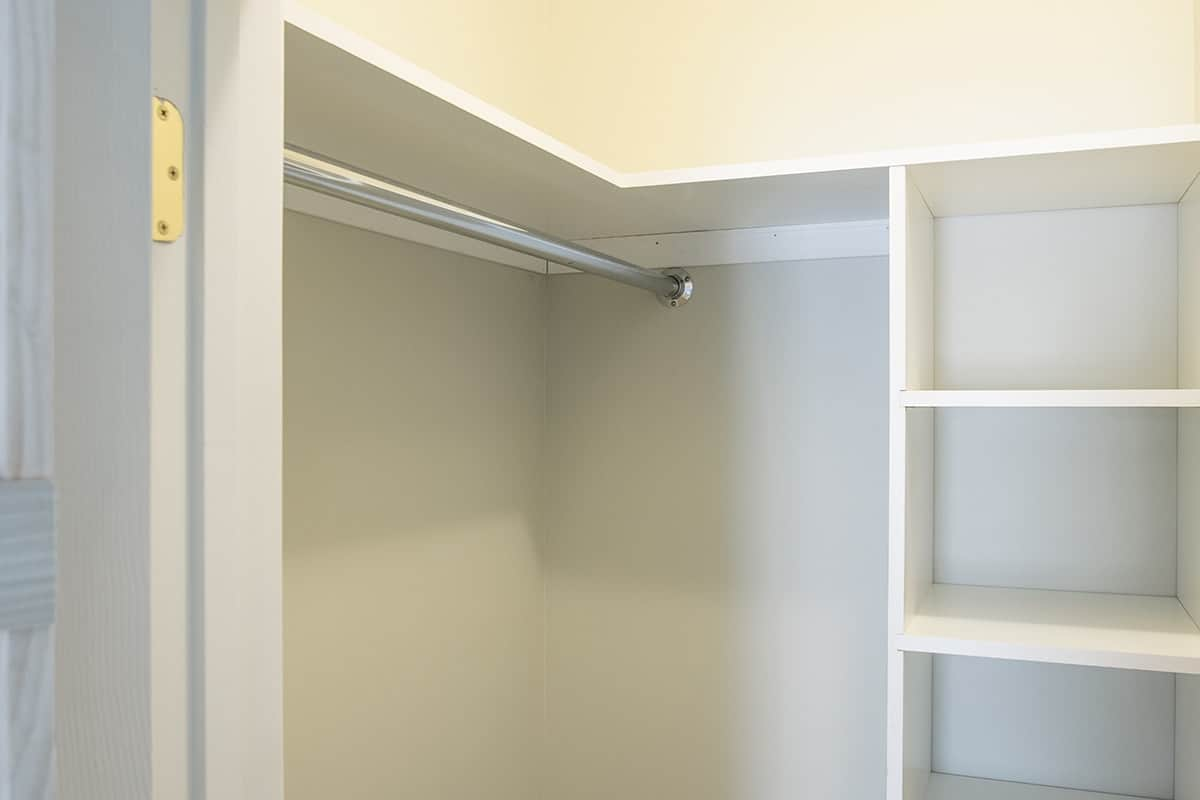 Custom built white shelving in walk-in closet with metal bar for hanging clothes.