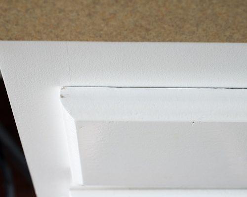 Corner detail on white cabinet panel
