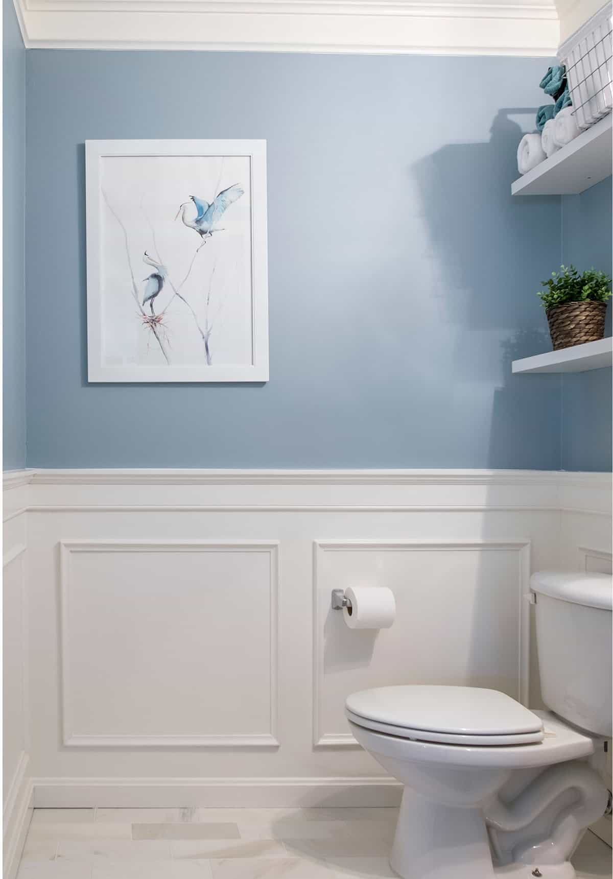 Blue Powder room decor reveal - this traditional half bathroom got a full makeover with a blue paint project, wainscoting, and marble floors.