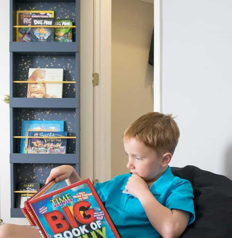 Boy reading book in front of bookshelf on closet door.