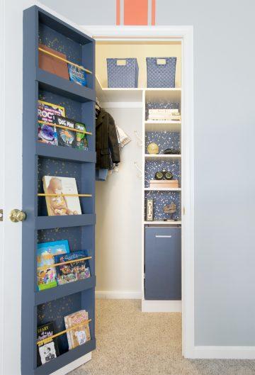 Boy's blue bedroom closet with open door revealing shelving, laundry hamper, and book shelf on the back of the door.