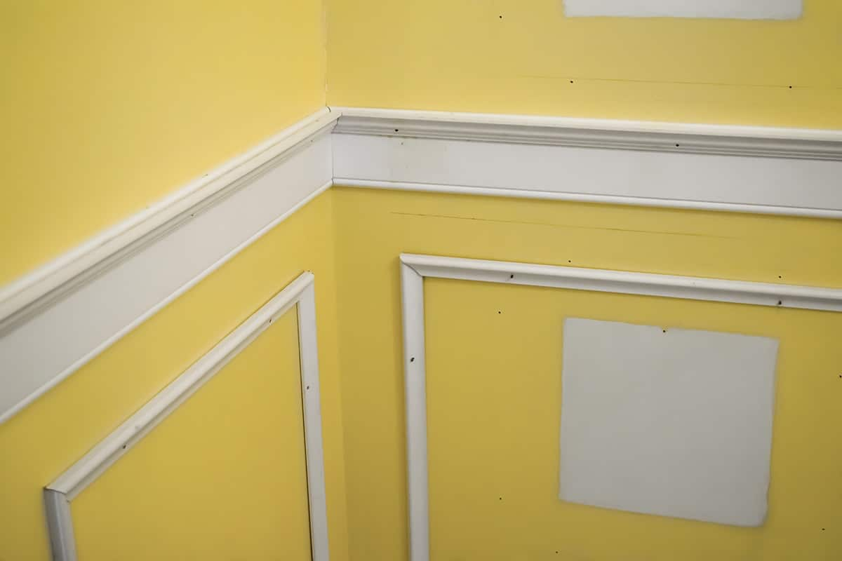 White wainscoting being added to corner of bright yellow wall in bathroom.