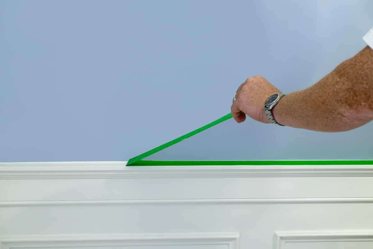 Frog tape being removed from top of wainscoting after painting main wall blue.
