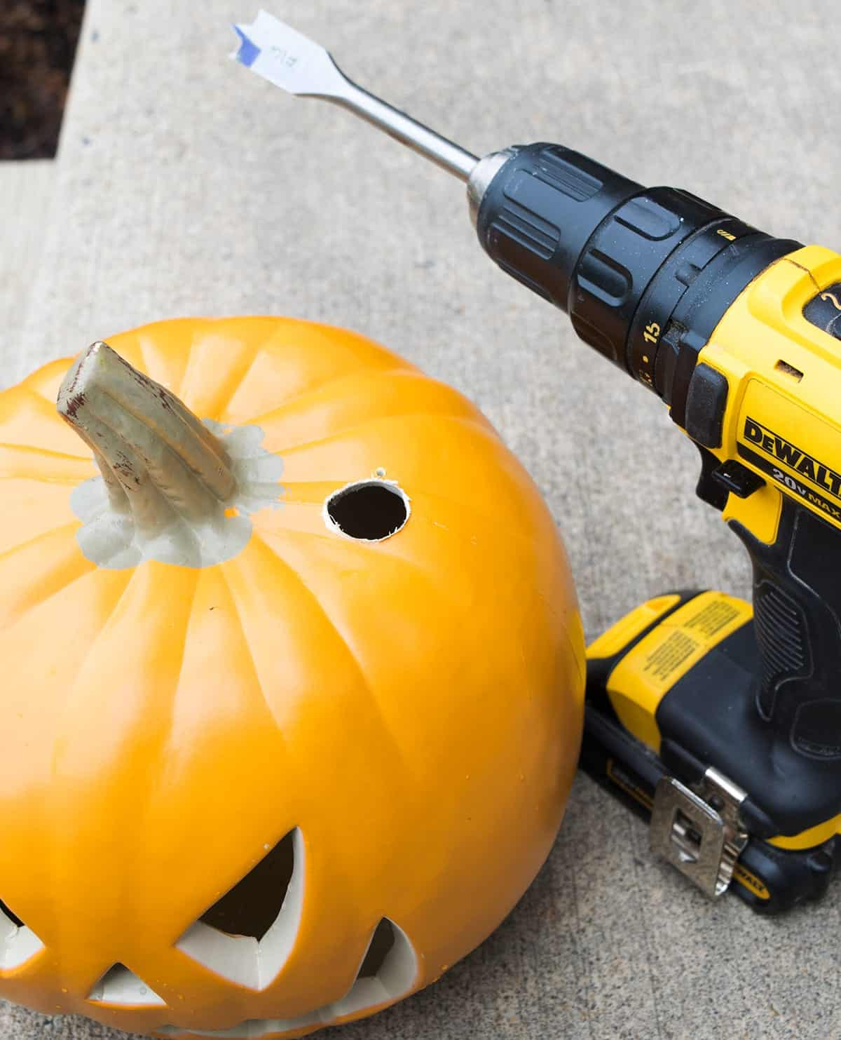 Carvable orange pumpkin next to drill with hole drilled out for stacking on wooden dowel.