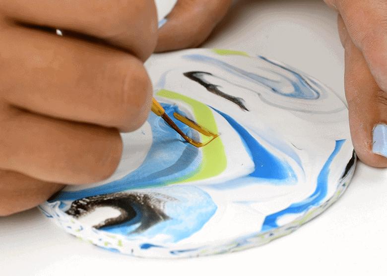 Painting gold monogram lettering on handmade mosaic coasters