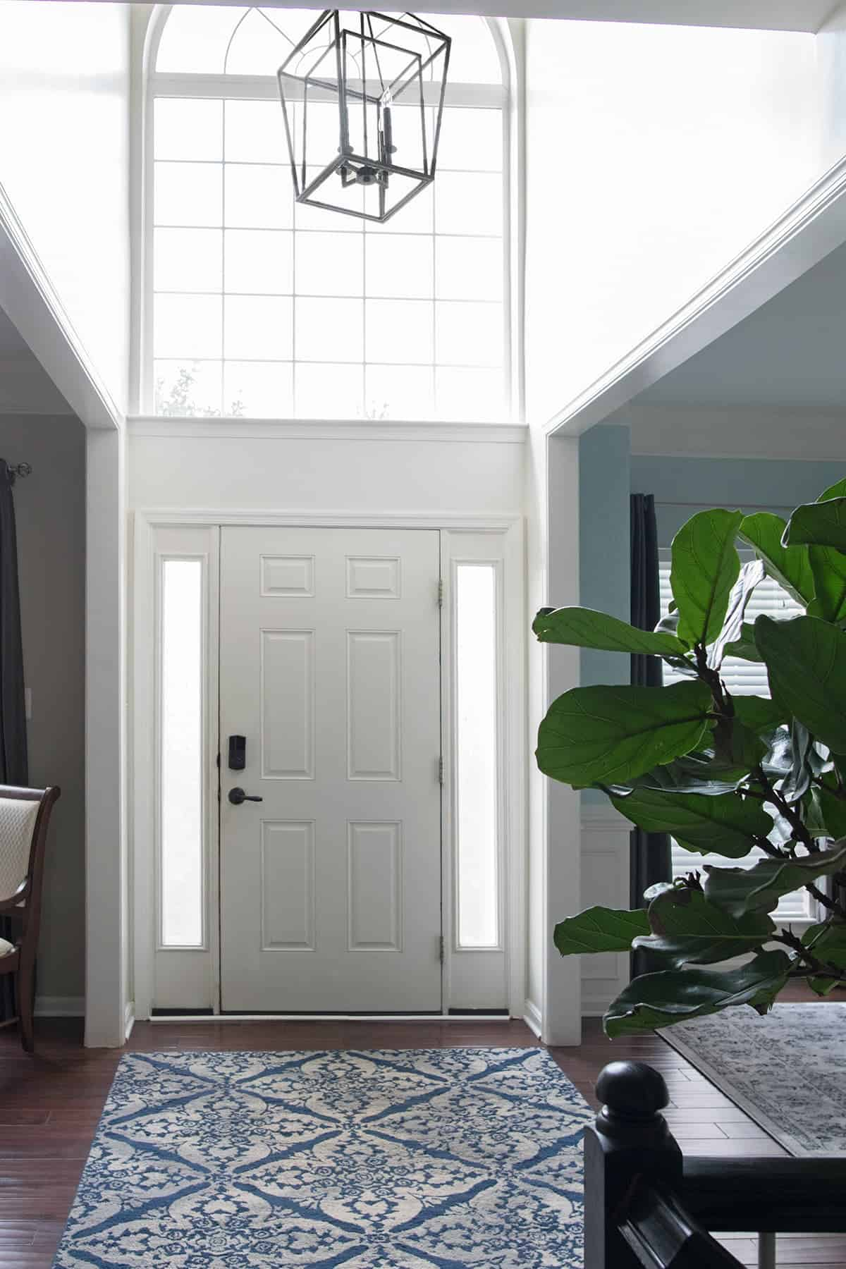 Front door facing view of open, two story foyer with hanging black Hudson Cage Lantern