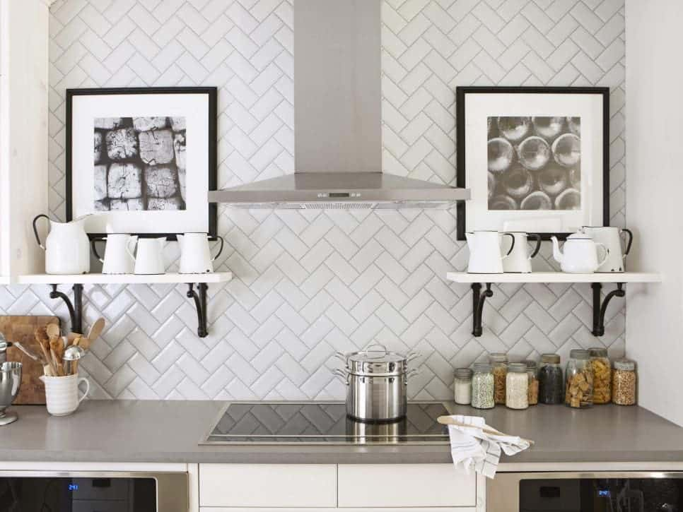 Beautiful white kitchen subway tile in herringbone pattern with free floating shelves