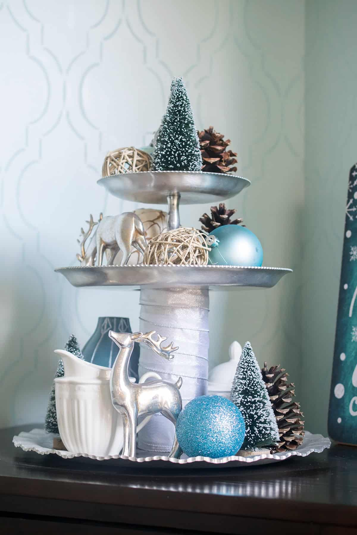 3 tiered silver stand decorated for Christmas with silver deer, pinecones, blue ornaments, and bottle brush trees