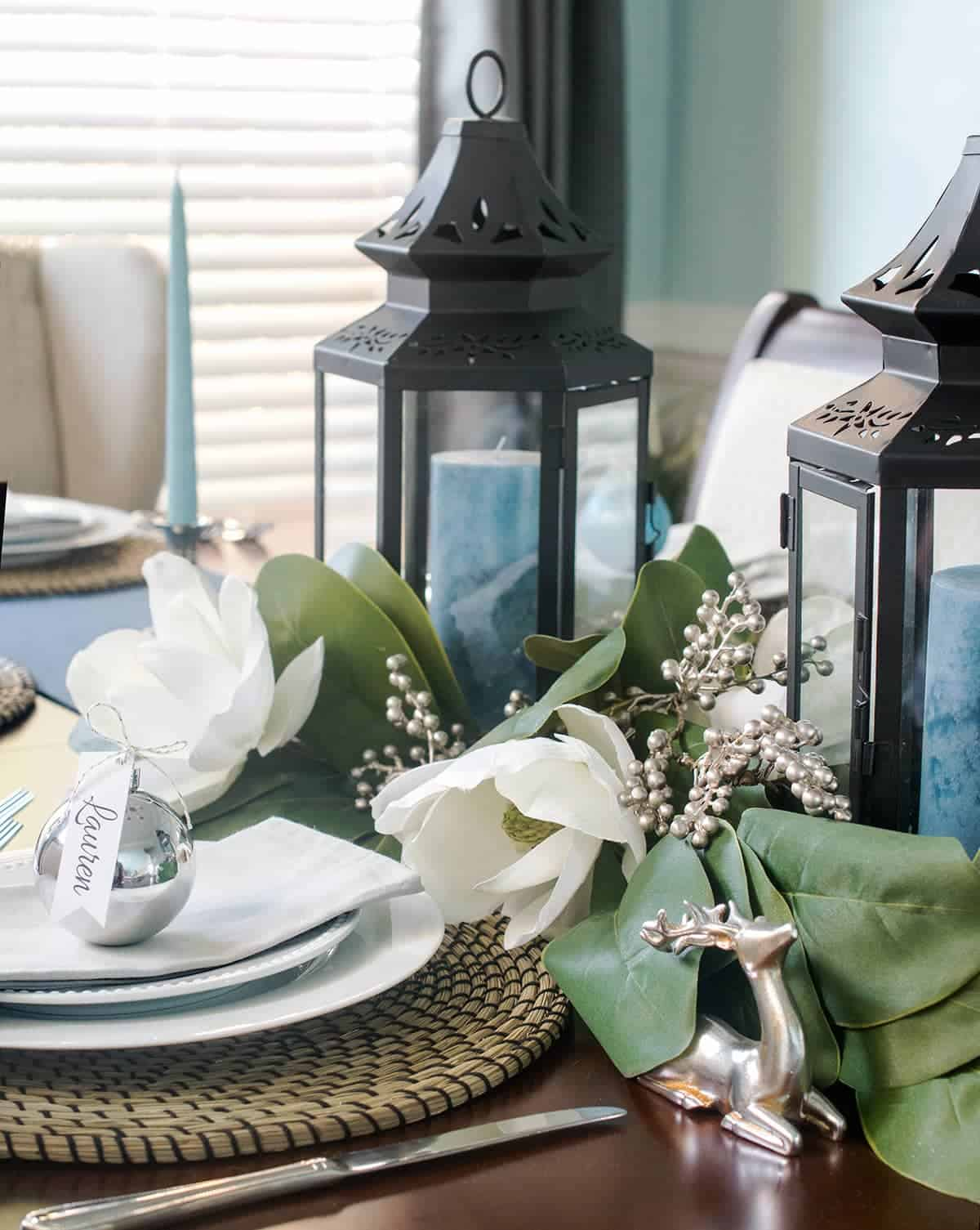 Christmas table setting with blue candles inside black lanterns.  Magnolia flower garland. Silver ornament, deer, and berry accents.