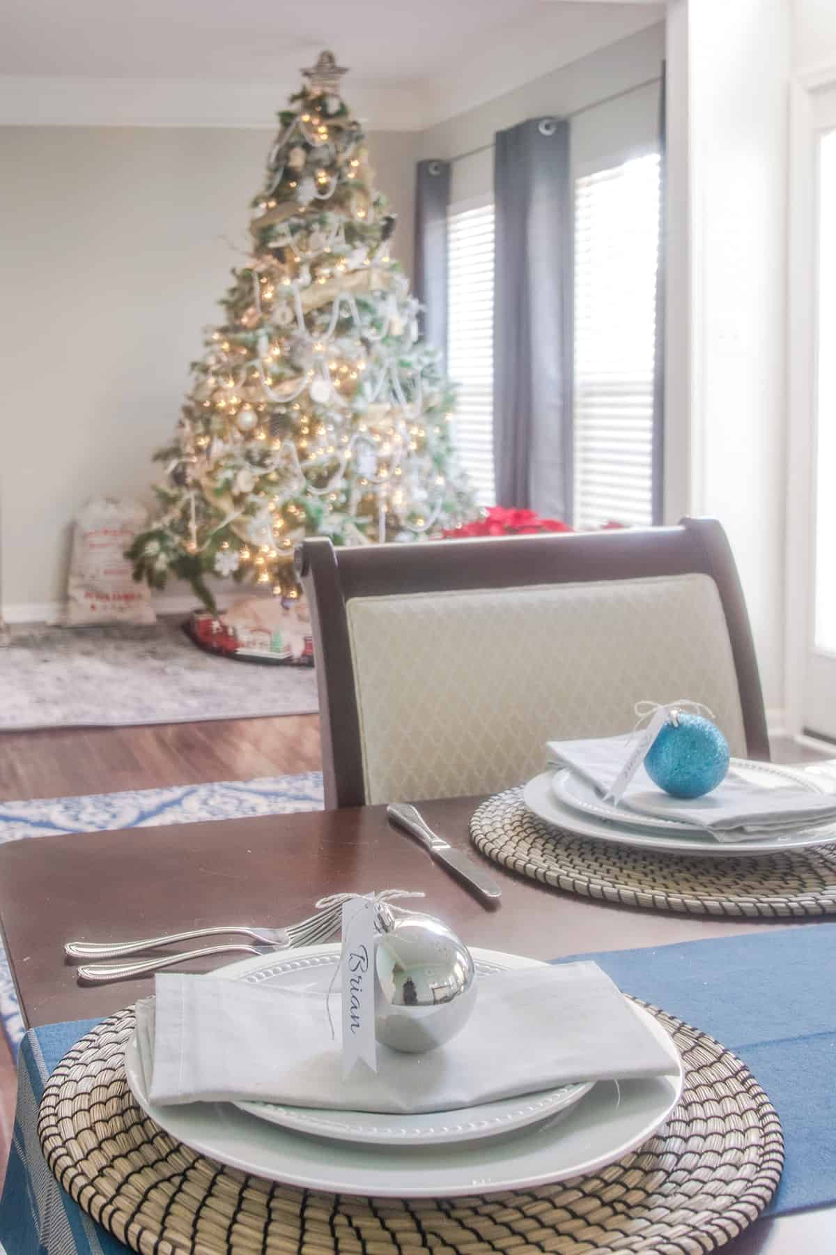 Winter wonderland dining room Christmas tablescape with woodland Christmas tree in background
