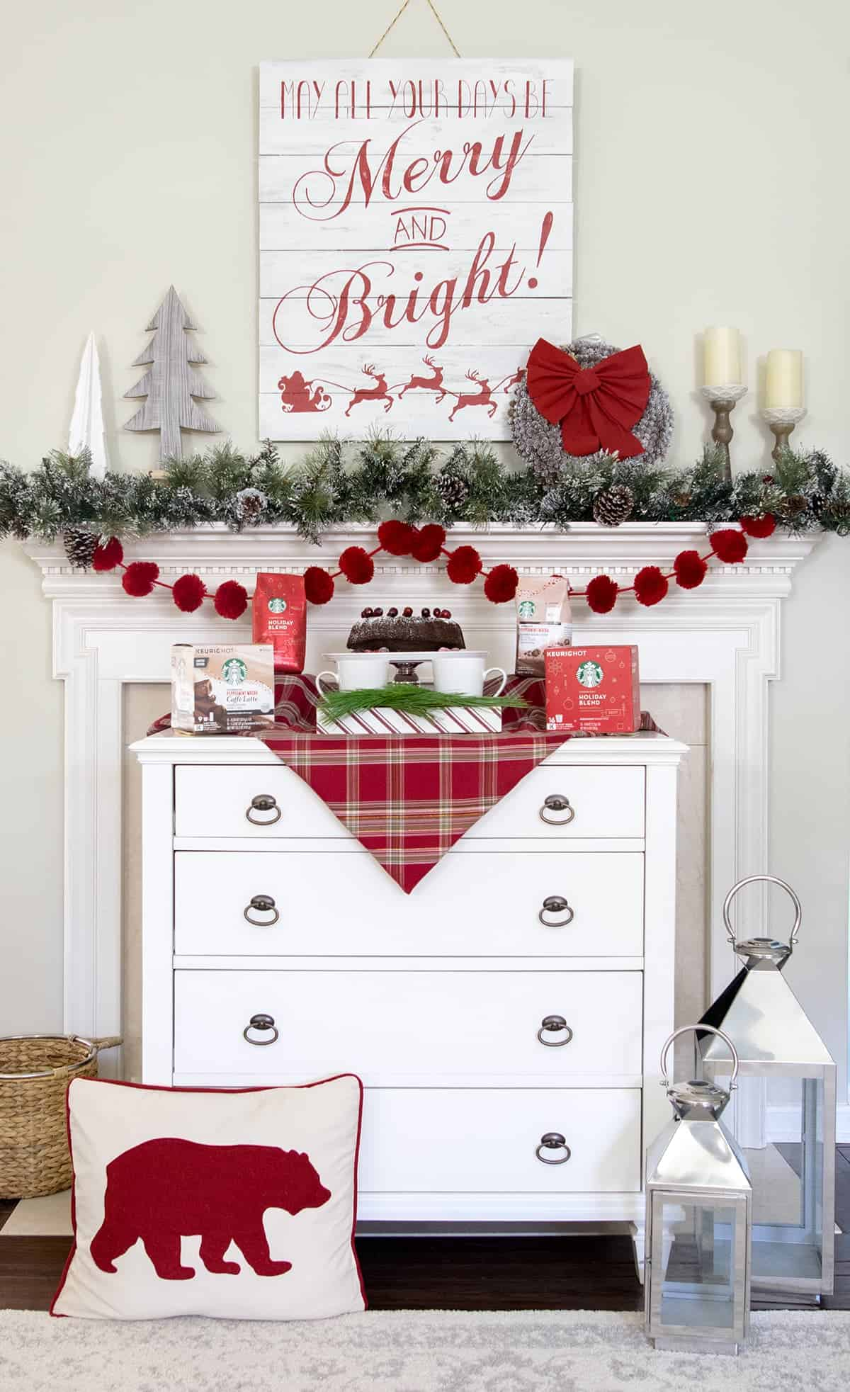 Mantle decorations and dessert bar for a holiday party. Red pom poms, snowy garland, Christmas tree shapes, Merry & Bright sign and candlesticks compliment colors on the makeshift buffet.