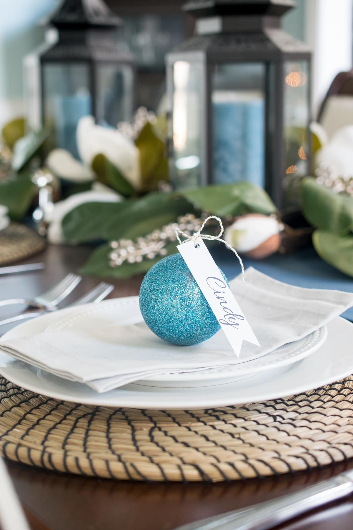 Personalized table setting with sparkly blue ornaments with name cards on white dinnerware and neutral mat