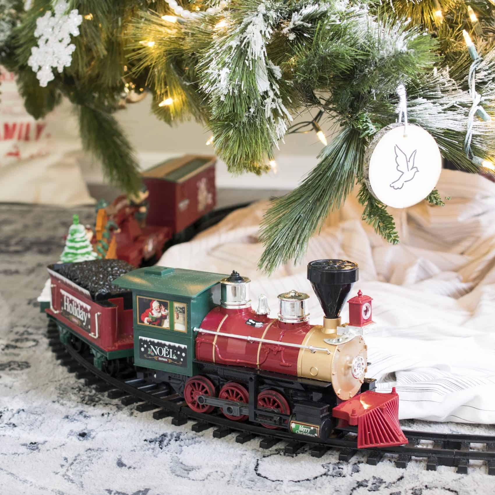 Close up of toy train track around bottom of tree..