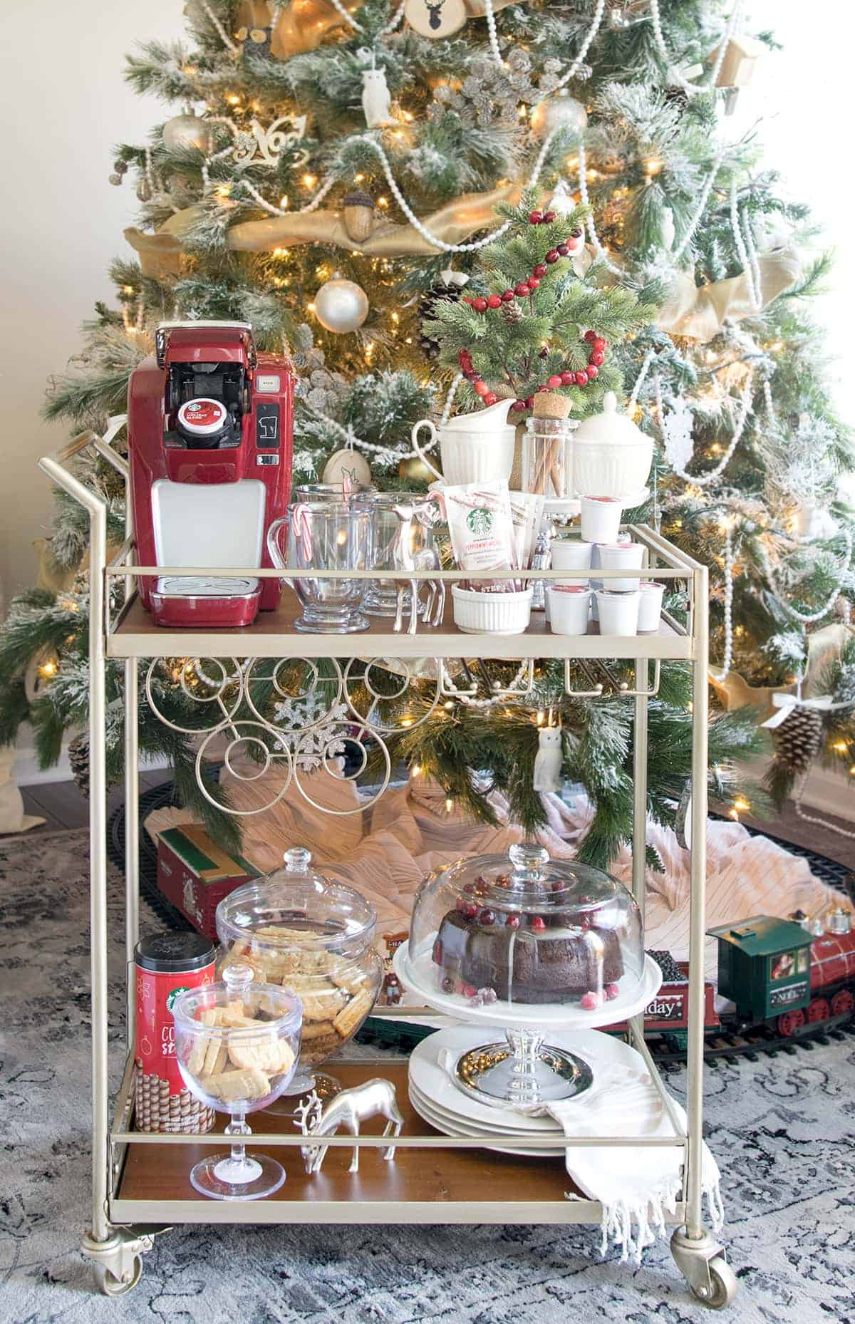 Coffee cart complete with coffee maker, cups, single pod coffees and all the fixings. Dessert cases and dessert plates line the bottom shelf of cart. Christmas tree with toy antique train in background.
