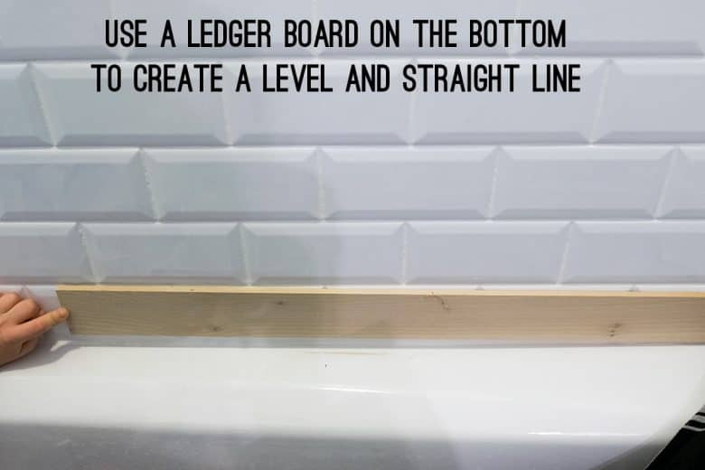 A ledger board being held up for tiling a wall.