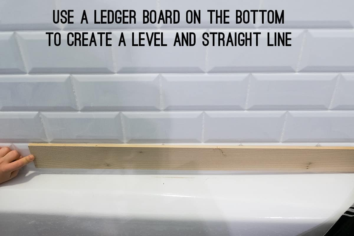 Using a wood ledger board to ensure rows are level when tiling large surface areas