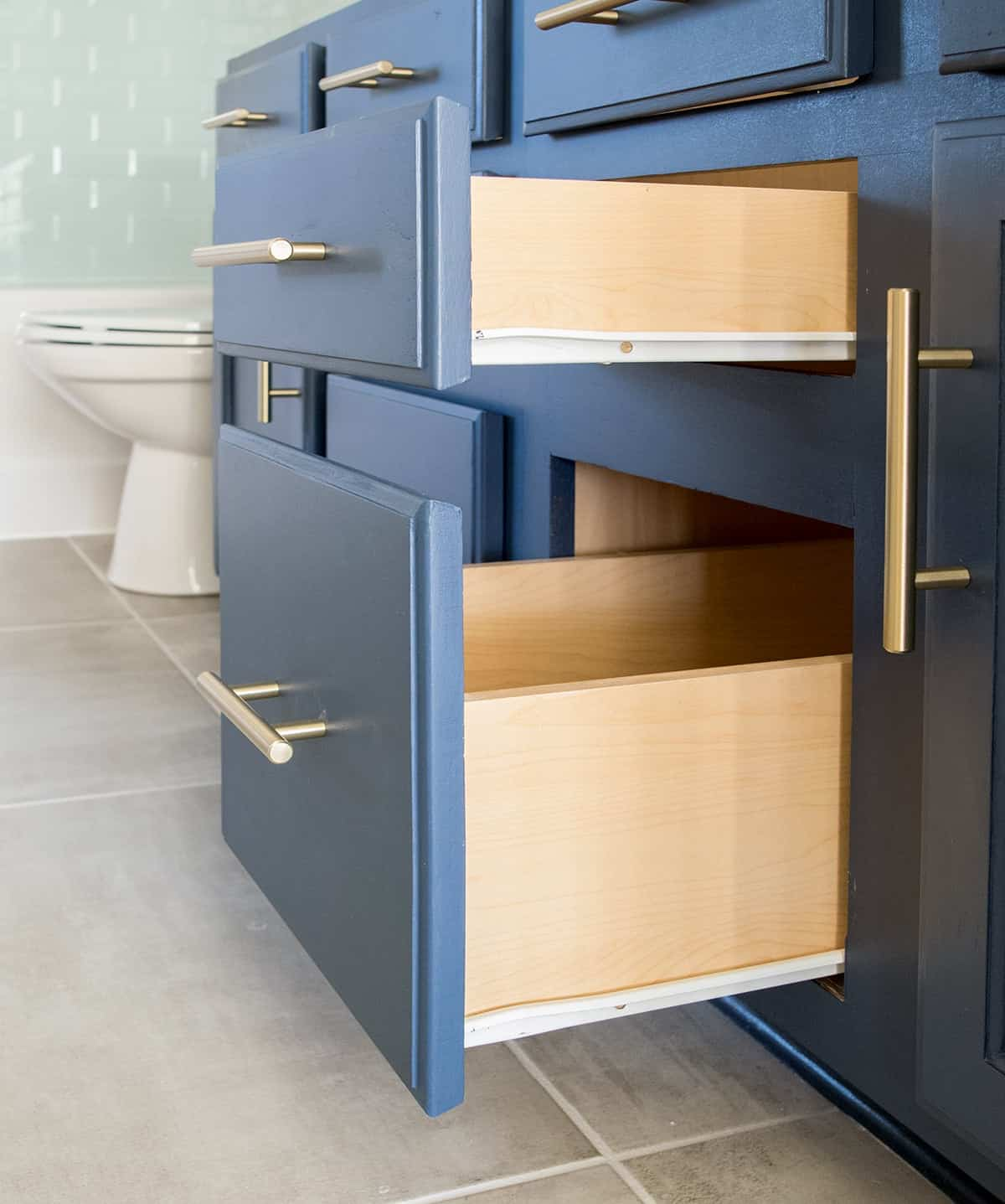 Closeup of sliding drawers in newly upgraded navy painted cabinet with brass hardware