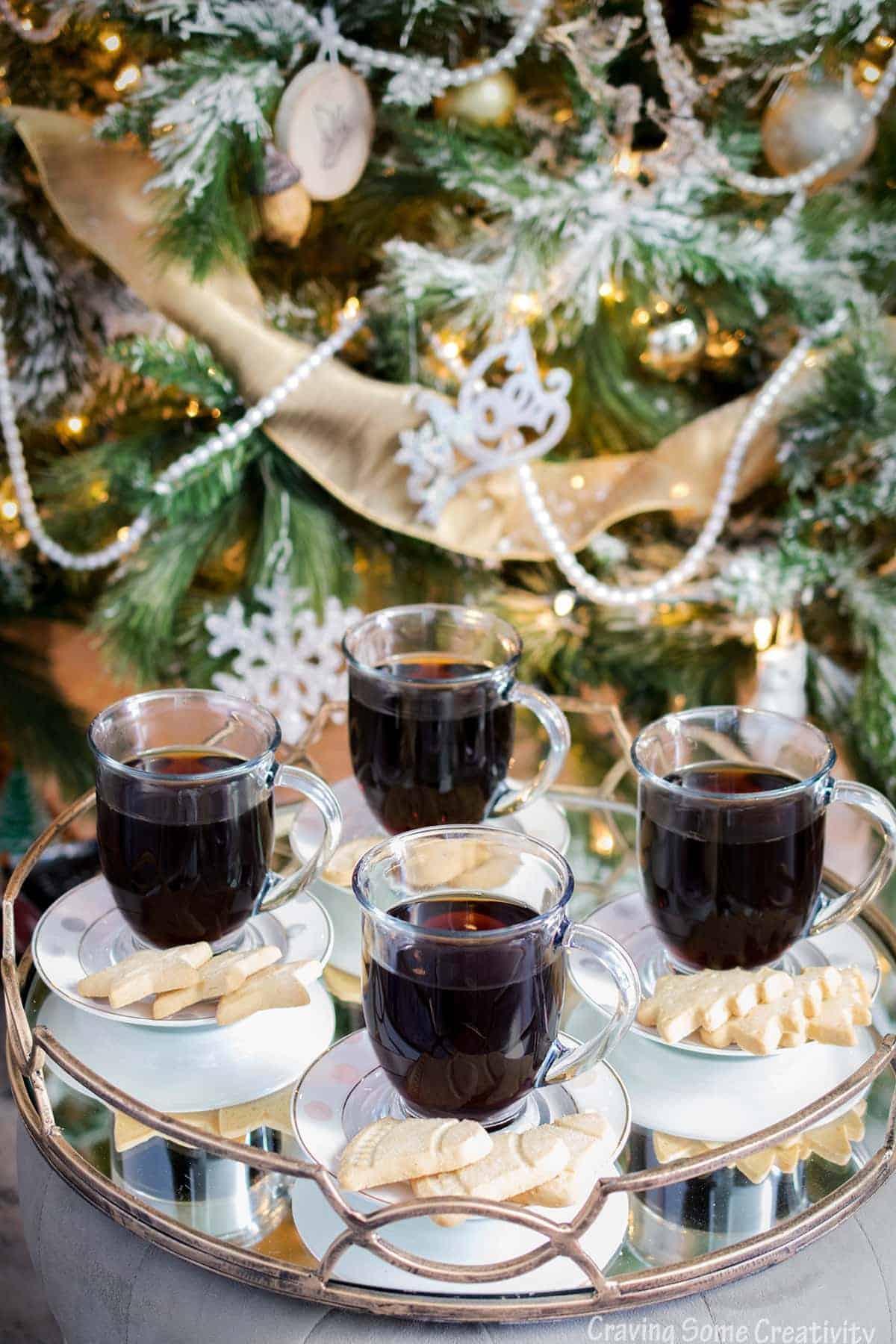 Coffee in mugs with a signature coffee drink and served with small cookies on the side. White and gold accented tree in background.