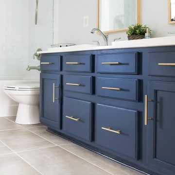 Midnight blue vanity with brass handles in a grey and white bathroom.