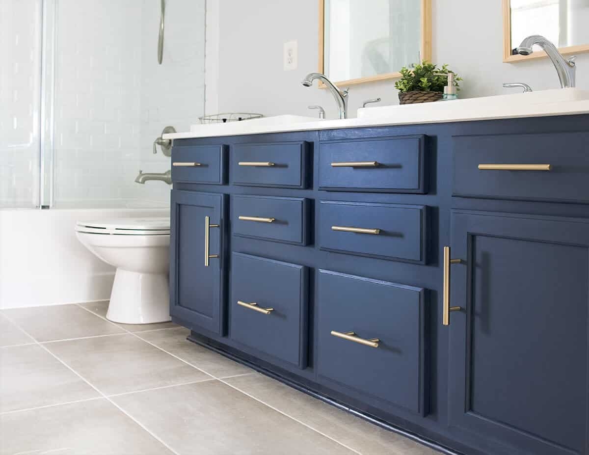 Painted navy blue vanity with brass hardware in a bathroom.