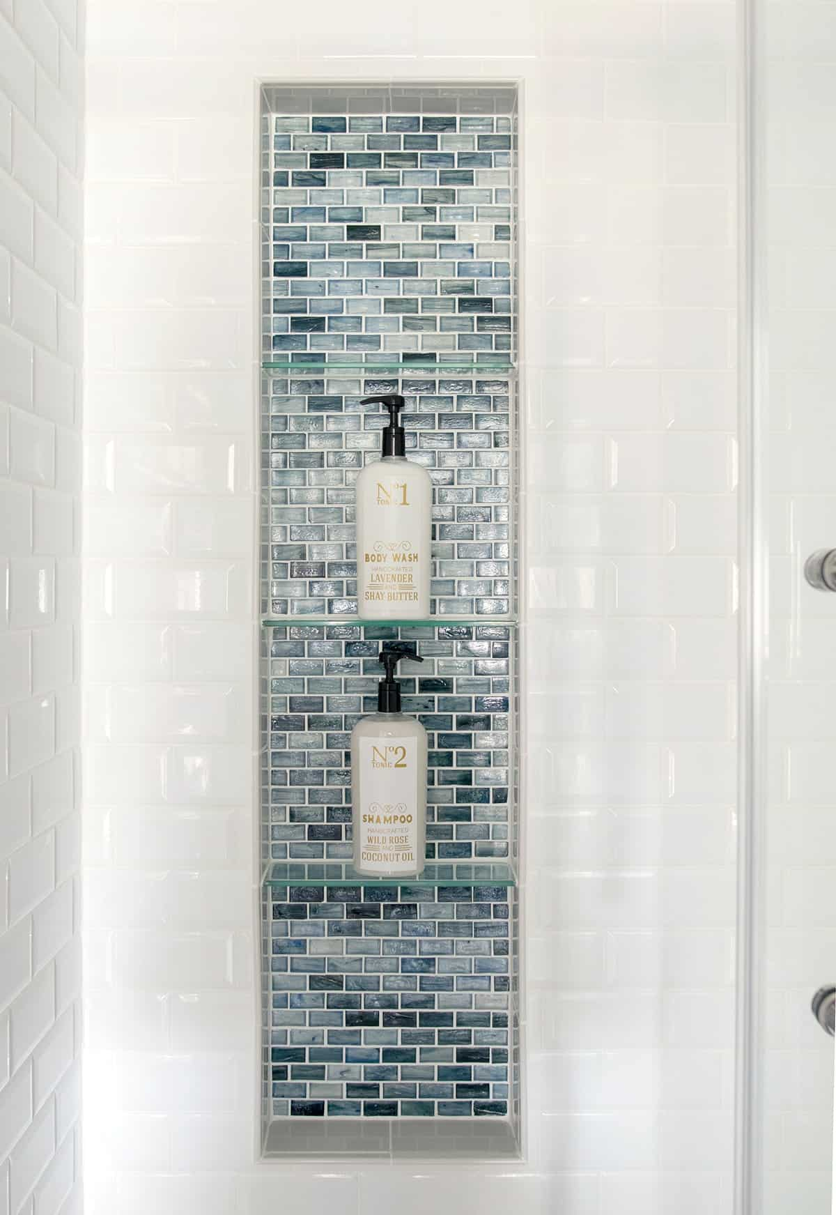 large shower niche with glass tiles and glass shelves. Blue glass shower inset with white subway tile surround