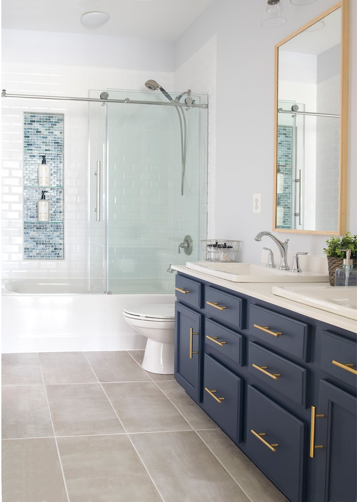 Modern bathroom remodel including navy blue vanity, glass shower, tile flooring. Modern traditional in in style.