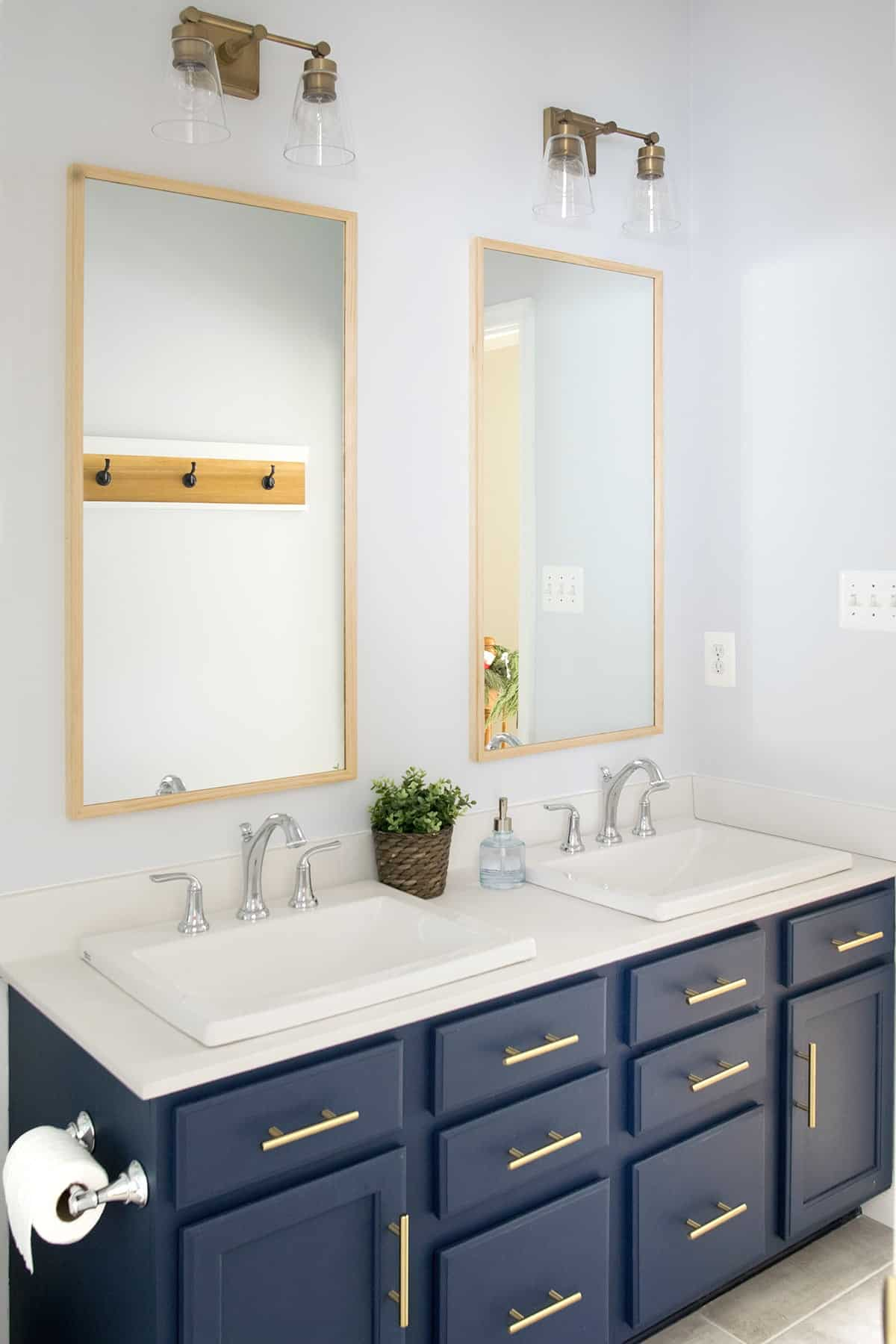 Navy Bathroom vanity with brass handles, drop in sinks and vintage faucets.