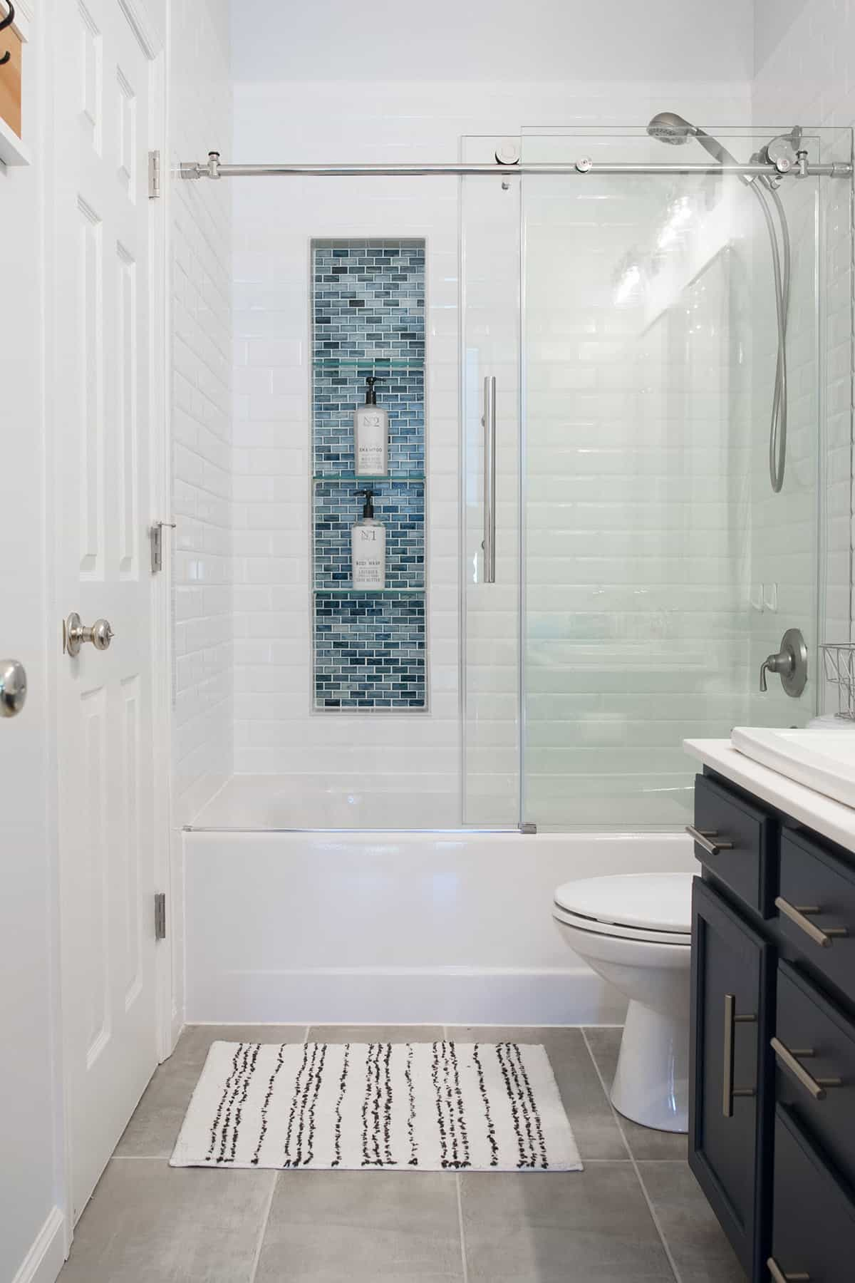 Acrylic tub with sliding glass shower door and mosaic tiled shower inlay in modern classic guest bathroom.