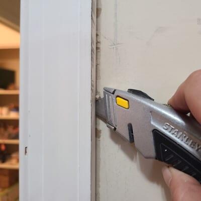 Razor knife cutting caulk around door casing.