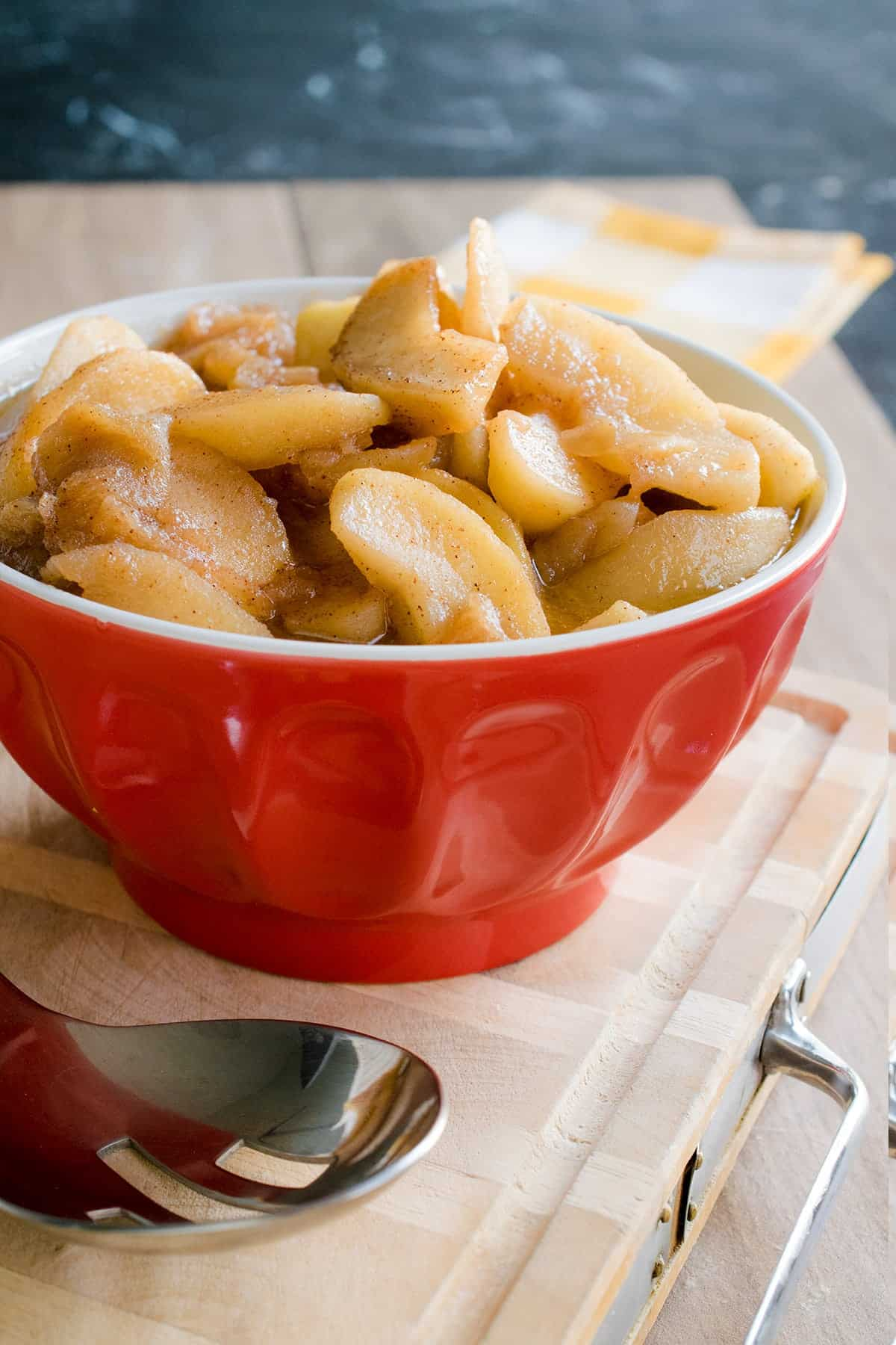 Southern fried apples with cinnamon in red serving bowl, a sweet and tangy southern tradition.
