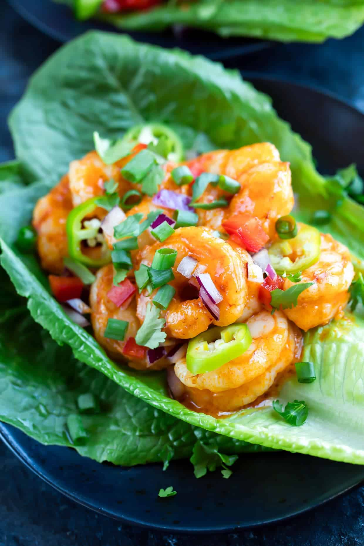 Buffalo Shrimp Lettuce Wraps with diced onion, tomato, and sliced jalapeno served on romaine lettuce