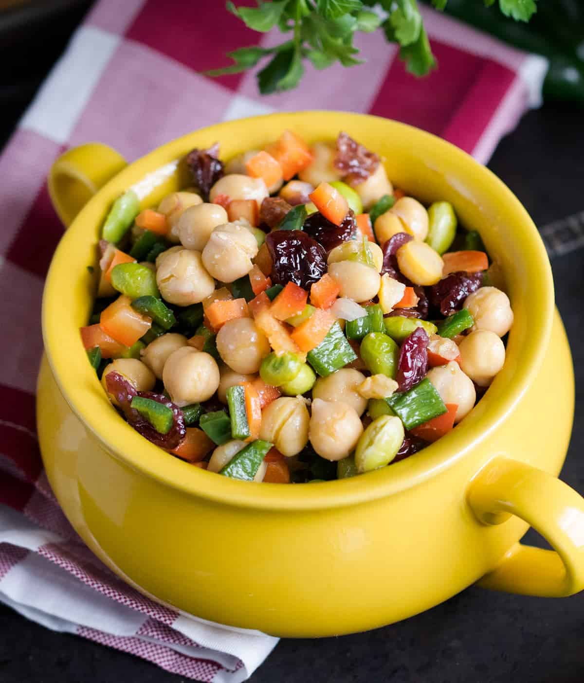 Chickpea Salad - A delicious chopped salad with lots of veggies, cranberries, and a tangy vinaigrette dressing in yellow crock