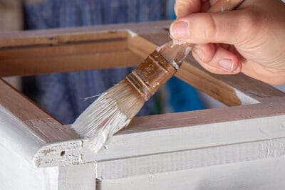 Painting a dresser white with a paintbrush.