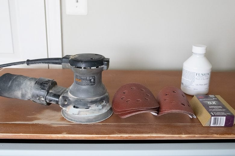 tools for painting furniture including orbital sander, sanding pads and blocks, and adhesive primer