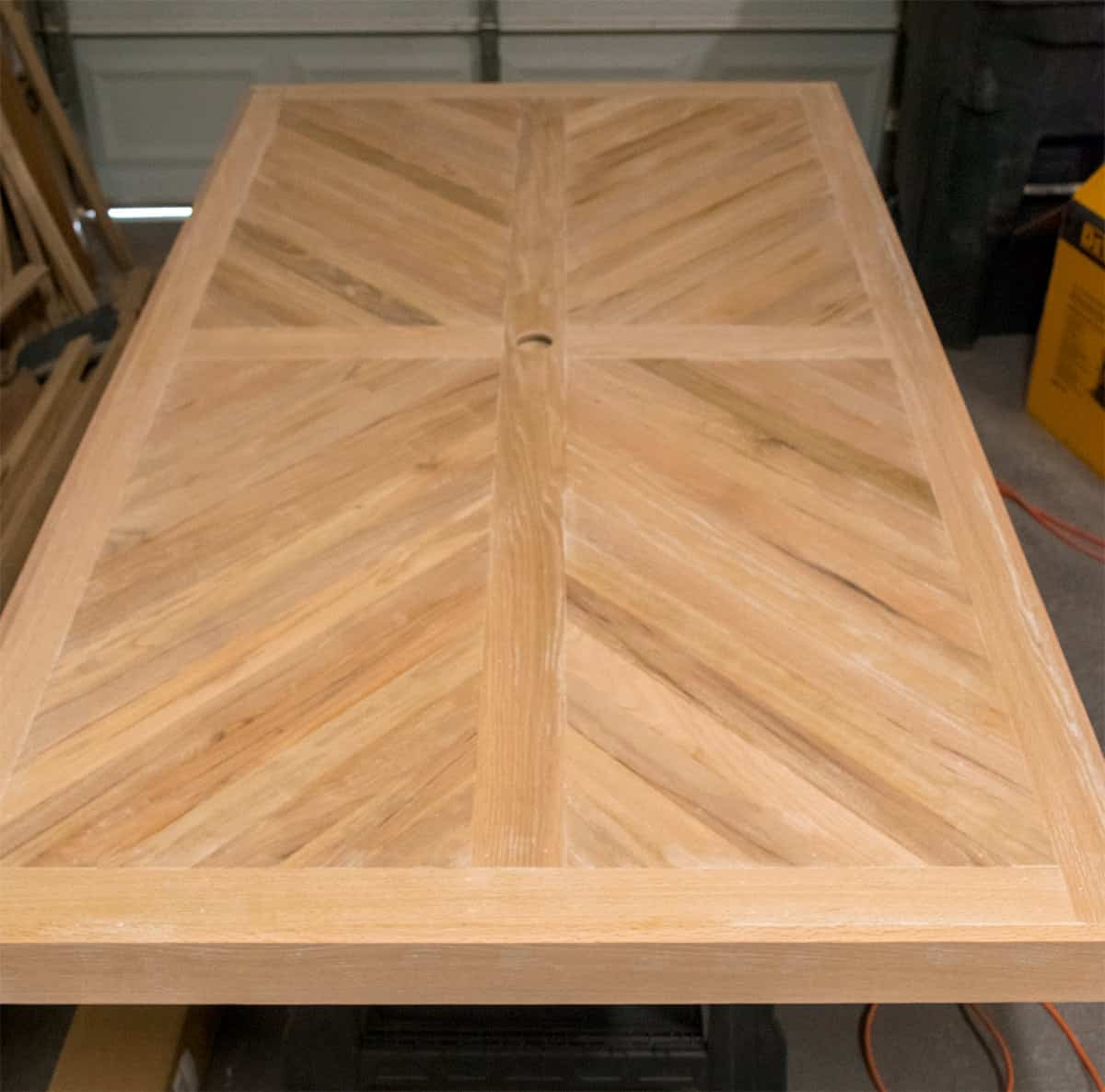 Reclaimed wood cross-X patterned patio table top using white oak hardwood.