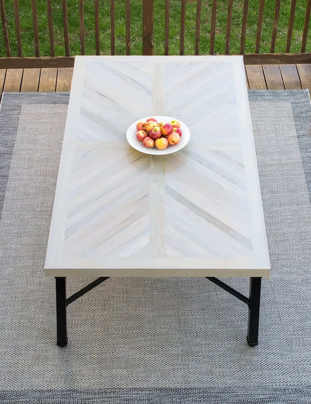 Refinished light gray outdoor dining table with white bowl of peaches in center on outdoor rug on deck.