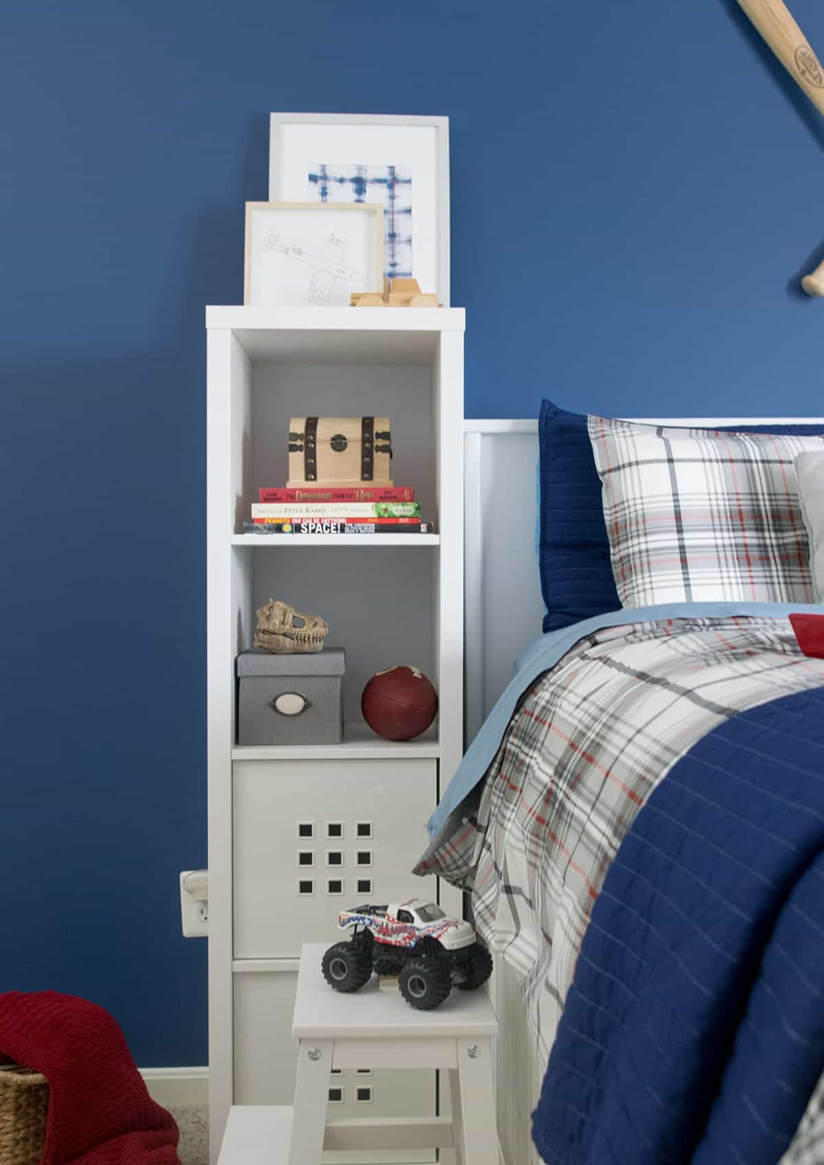 White bedside bookshelf next to captain's bed with blue walls and sports decor.